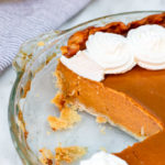 pumpkin pie in a glass pie dish with a slice missing