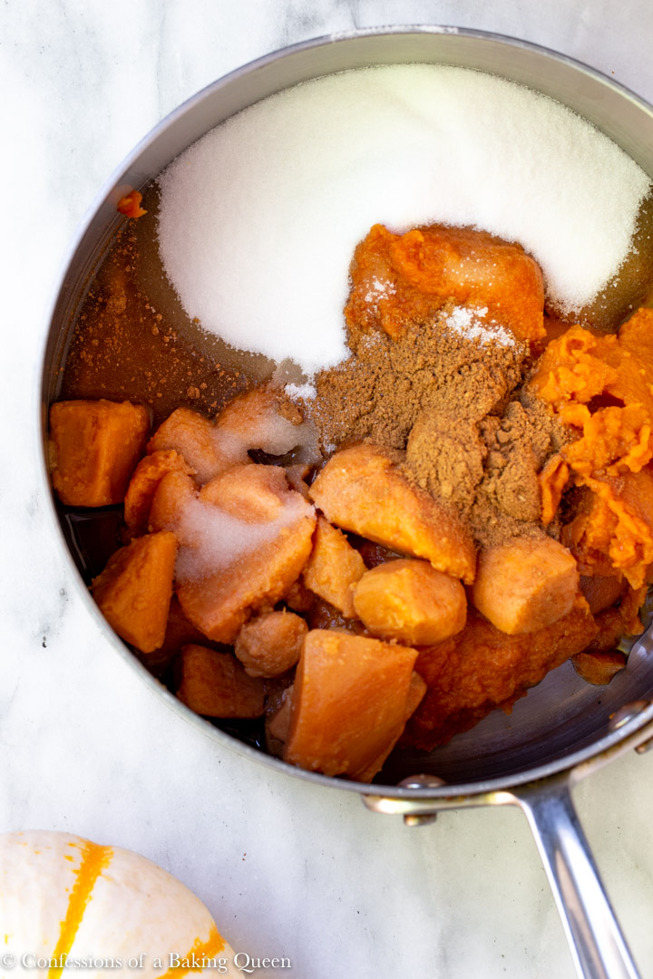 pumpkin, sugar, sweet potatoes and maple syrup in a large pot for a how to make pumpkin pie recipe
