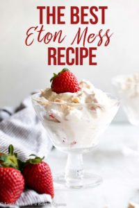 eton mess in a tall glass dish with a strawberry on top