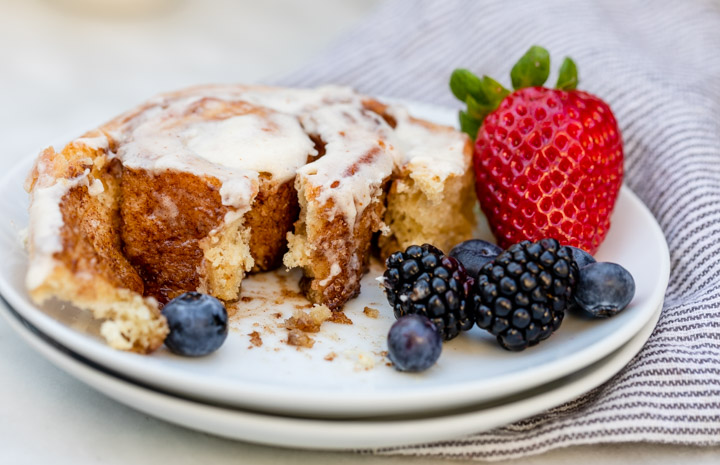 cinnamon roll cut open on a white plate with berries and white and blue linen on a white marble surface
