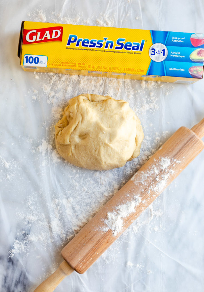 brown butter cinnamon roll dough on a glad press'n seal surface with a rolling pin and flour