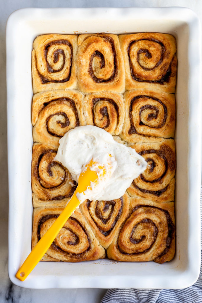 cream cheese frosting on a yellow spatula on top of just baked brown butter cinnamon rolls