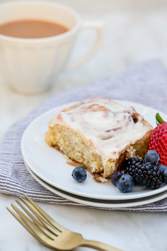 brown butter cinnamon roll on a  round plate with berries