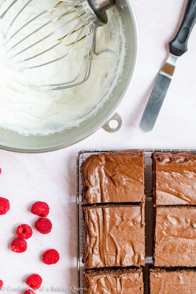 bowl of whipped cream next to brownie chocolate cheesecake bars