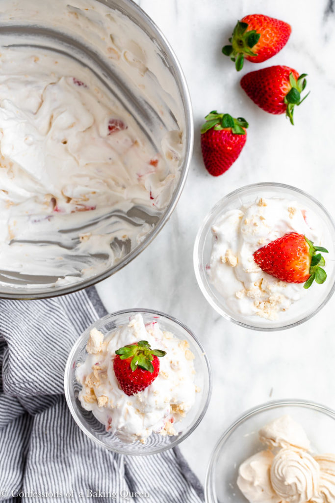 eton mess scooped into glass bowls  on a marble surface with a white and blue linen