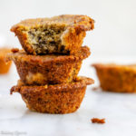 oat flour banana bread muffins stacked on top of each other on a white surface
