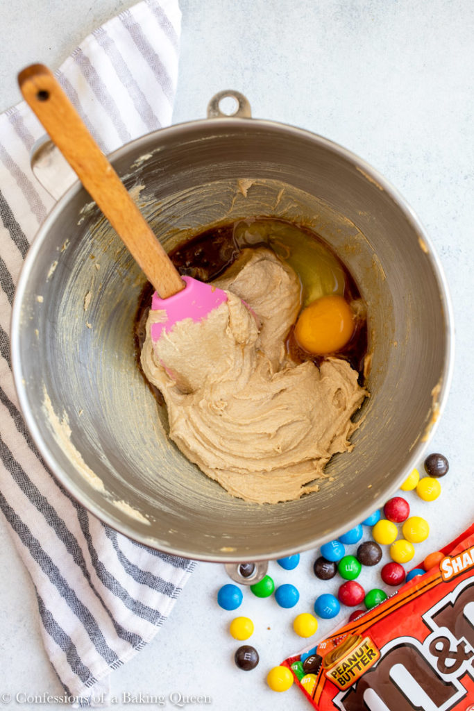 egg added to wet ingredients for a peanut butter m&m cookie recipe