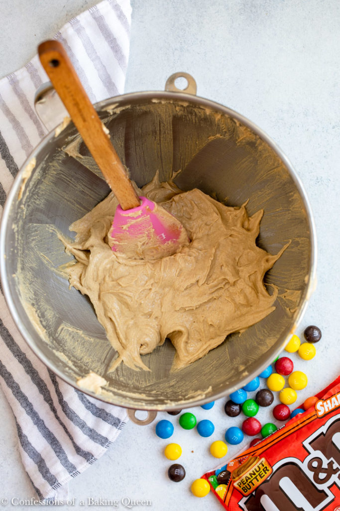 wet ingredients in a metal bowl for a peanut butter m&m cookie recipe