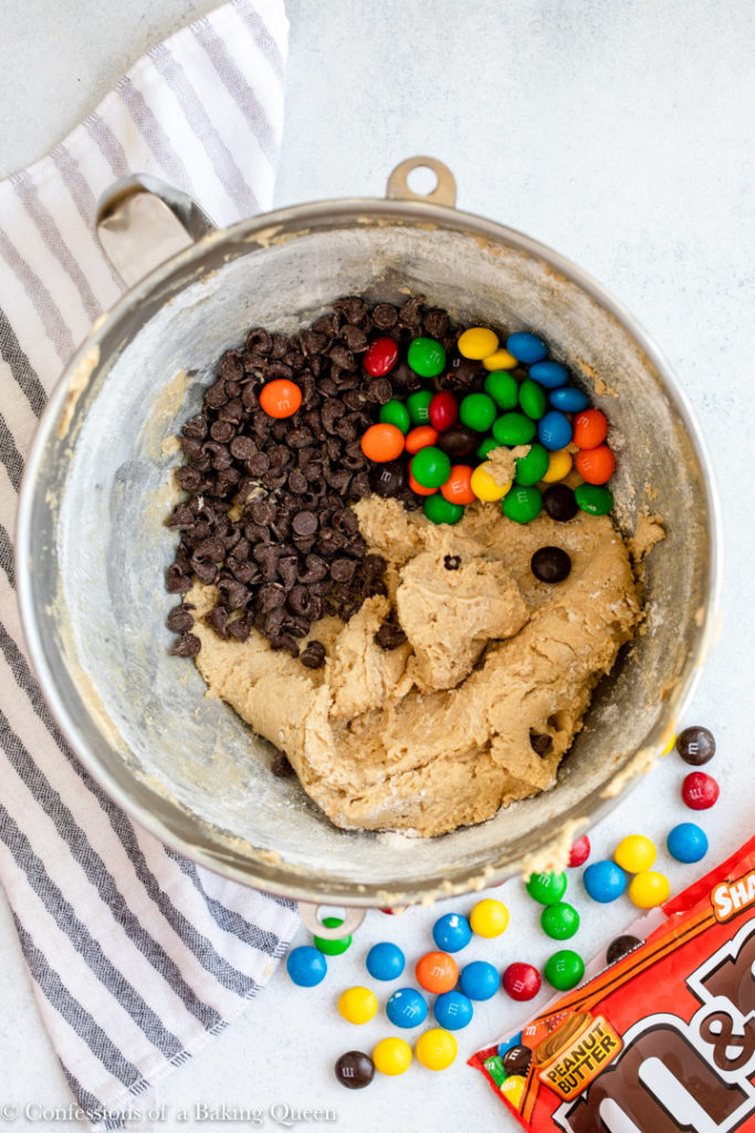 chocolate chips and peanut butter m&ms added to cookie dough on a white marble surface with a white and grey linen and open bag of m&ms spilling out