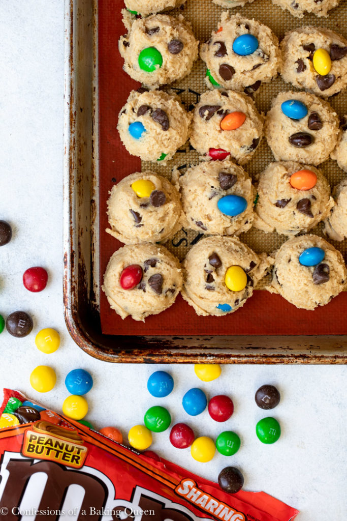 peanut butter m&m cookie dough scooped on a silpat lined baking sheet on a white marble surface with a bag of m&ms spilling out
