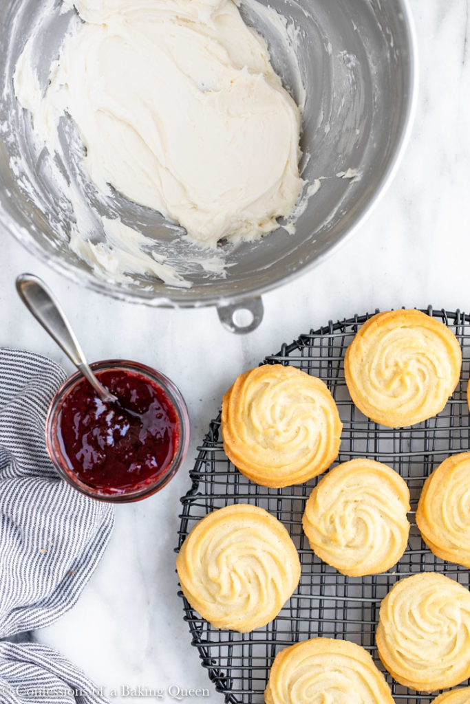viennesse whirl biscuits with a pot of strawberry jam and a metal bowl of buttercream