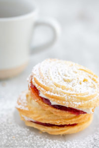viennese whirl with powdered sugar on top on a white surface with tea in the background