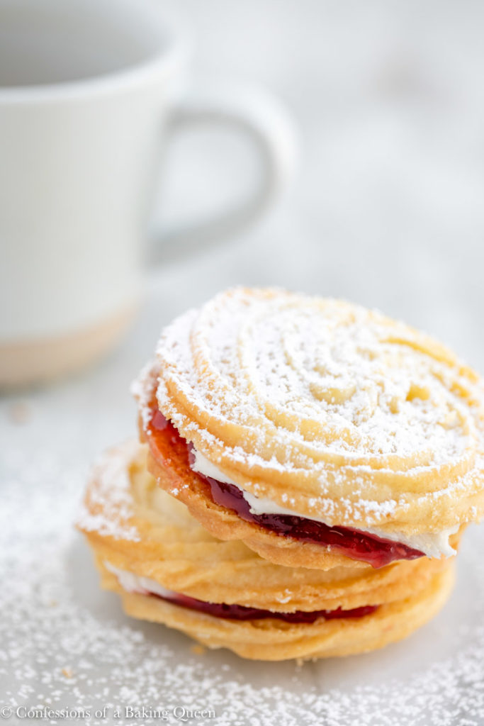 viennesse whirl with powdered sugar on top on a white surface with tea in the background