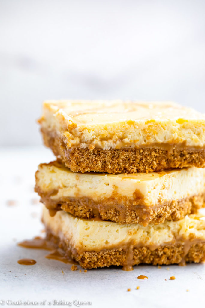 three dulce de leche cheesecake bars stacked on top of each other on a white surface