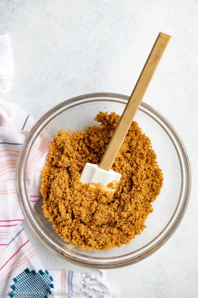 graham cracker crust ingredients all mixed together in a glass bowl
