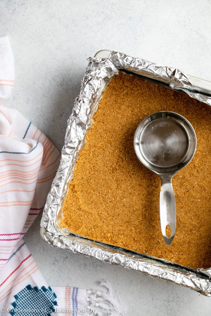 measuring cup on top of graham cracker crust in a foil lined square pan