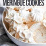 meringue cookies in a white bowl next to a blue and white towel