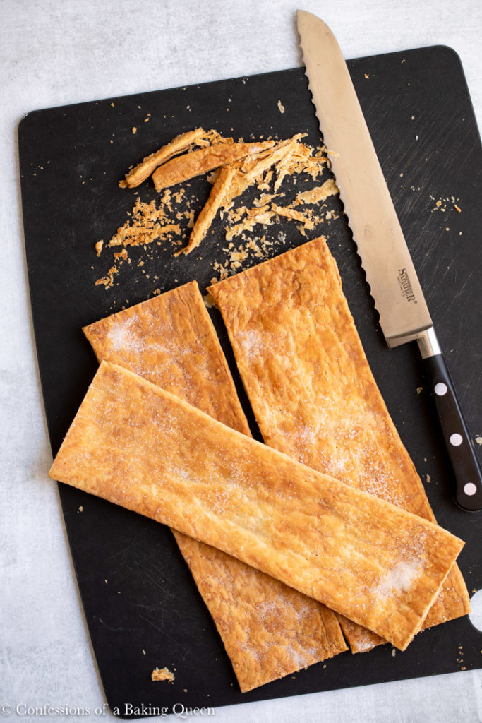 baked puff pastry sheets on a black cutting board with a knife