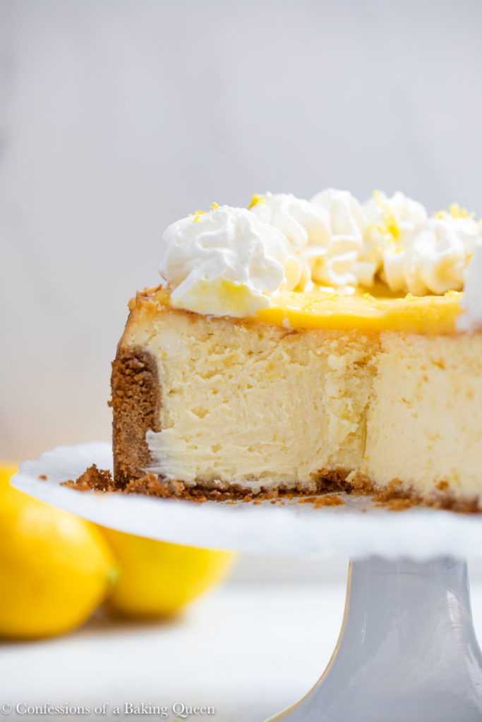 lemon curd cheesecake cut open on a white glass cake stand