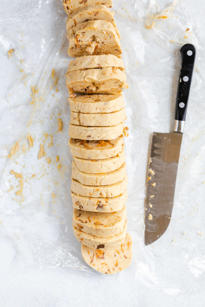 a knife and sliced cookie dough on a plastic wrap
