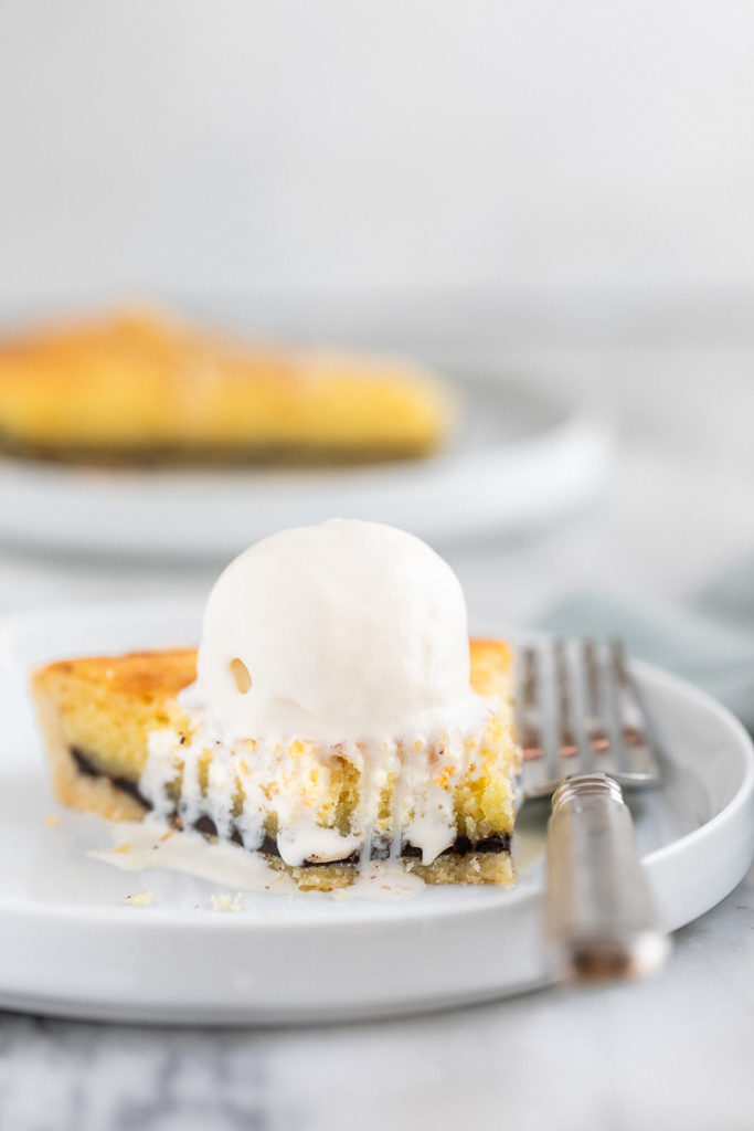 Orange Chocolate Frangipane Tart on a plate with ice cream and a fork