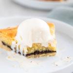 Orange Chocolate Frangipane Tart with a scoop of ice cream bitten into on a white plate