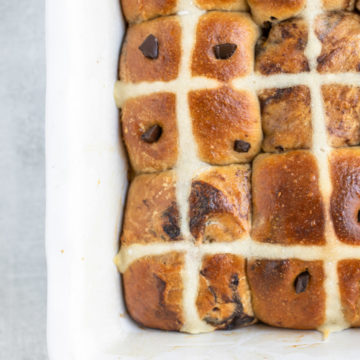 close up of chocolate hot cross buns in a rectangle ceramic dish