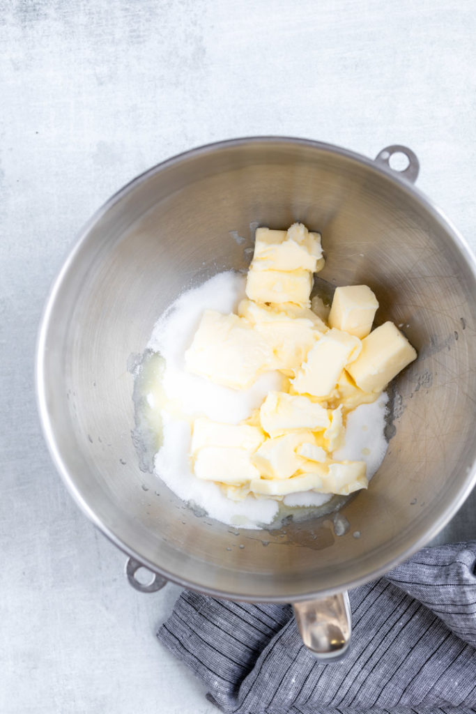 chunks of butter and granulated sugar in a metal mixing bowl