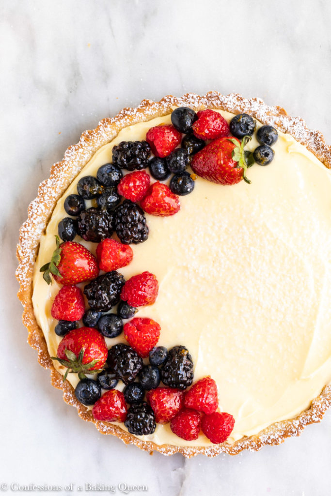 french lemon cream tart with berries on a marble surface