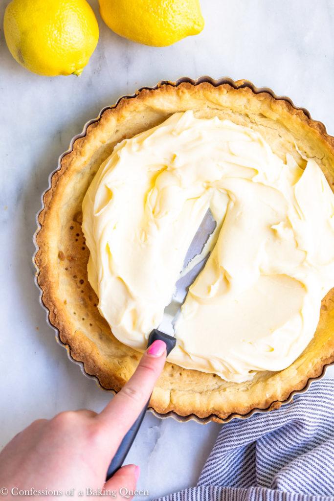 hand pushing lemon cream into a tart shell