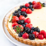 45 degree angle of a french lemon cream tart on a white surface