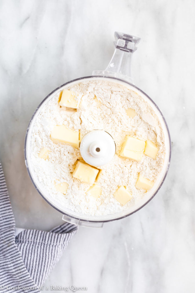 chunks of butter in a food processor full of flour
