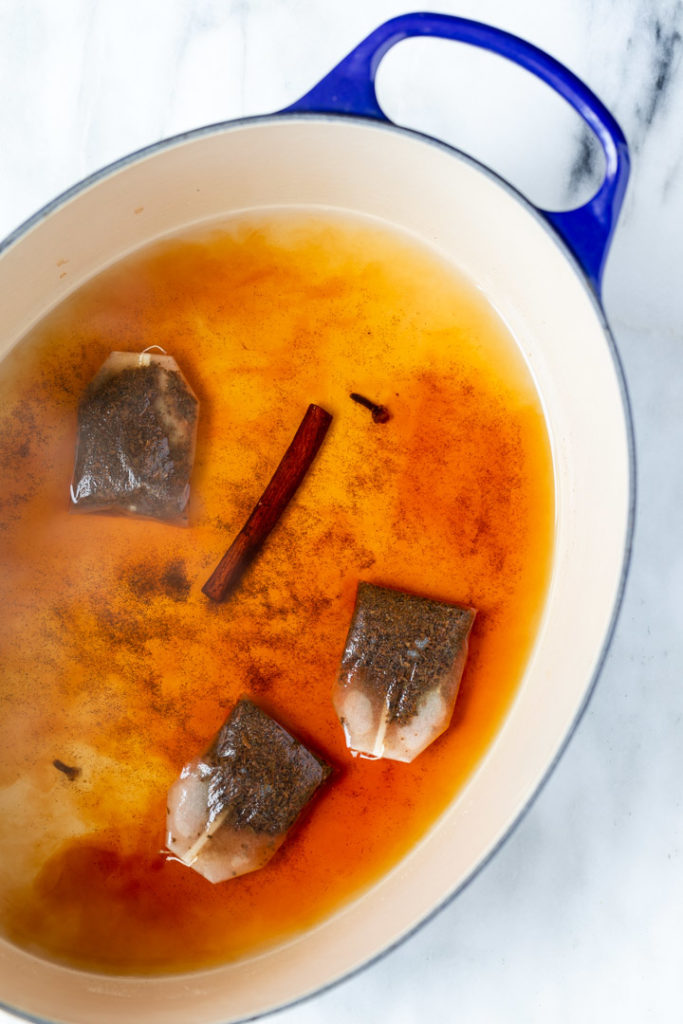 black tea bags added to water and spices in a large pot for a thai iced tea recipe