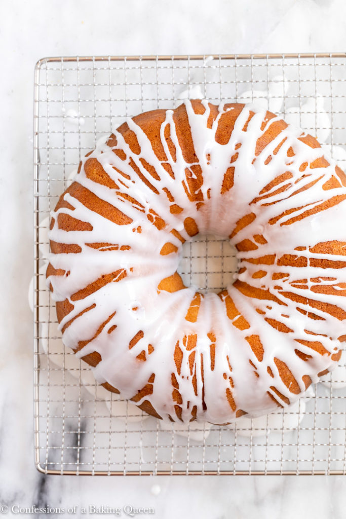 7up pound cake glazed on a wire rack on a white marble surface