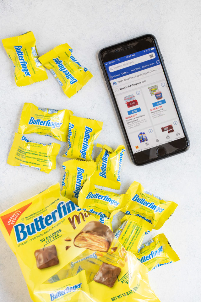i phone next to butterfinger candies spilling out of a bag