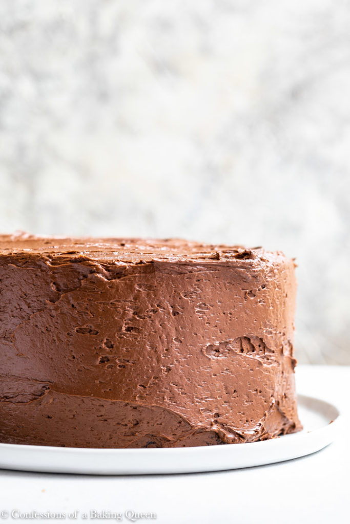 chocolate swiss meringue frosted cake on a white plate
