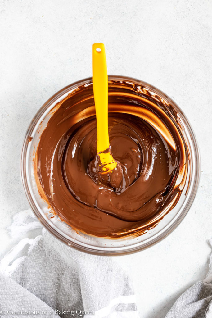 melted chocolate in a small glass bowl with a yellow spatula