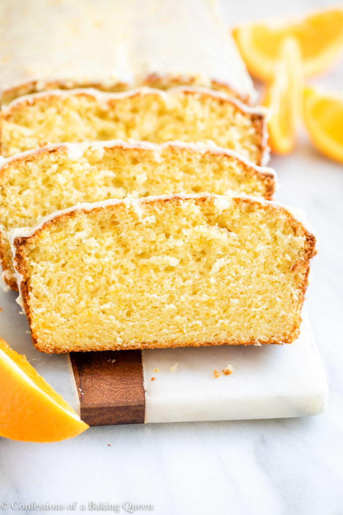orange loaf cake sliced on a white board