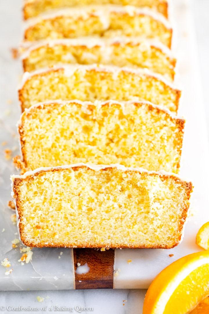 close up of orange loaf cake recipe on a white surface