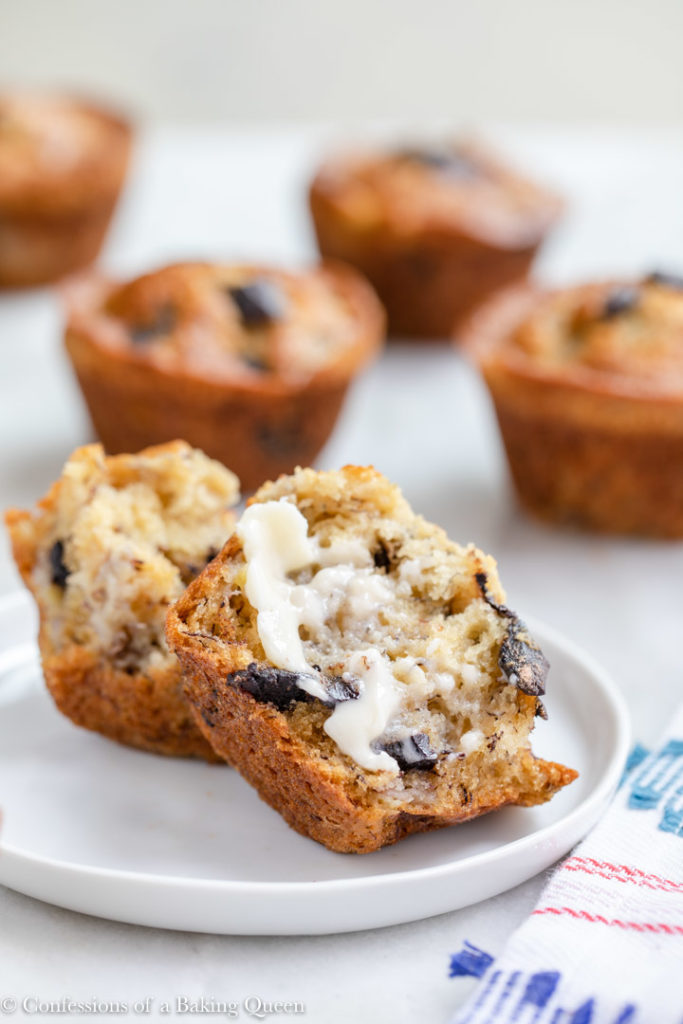 banana chocolate chip muffin pieces with butter on served on a small round plate