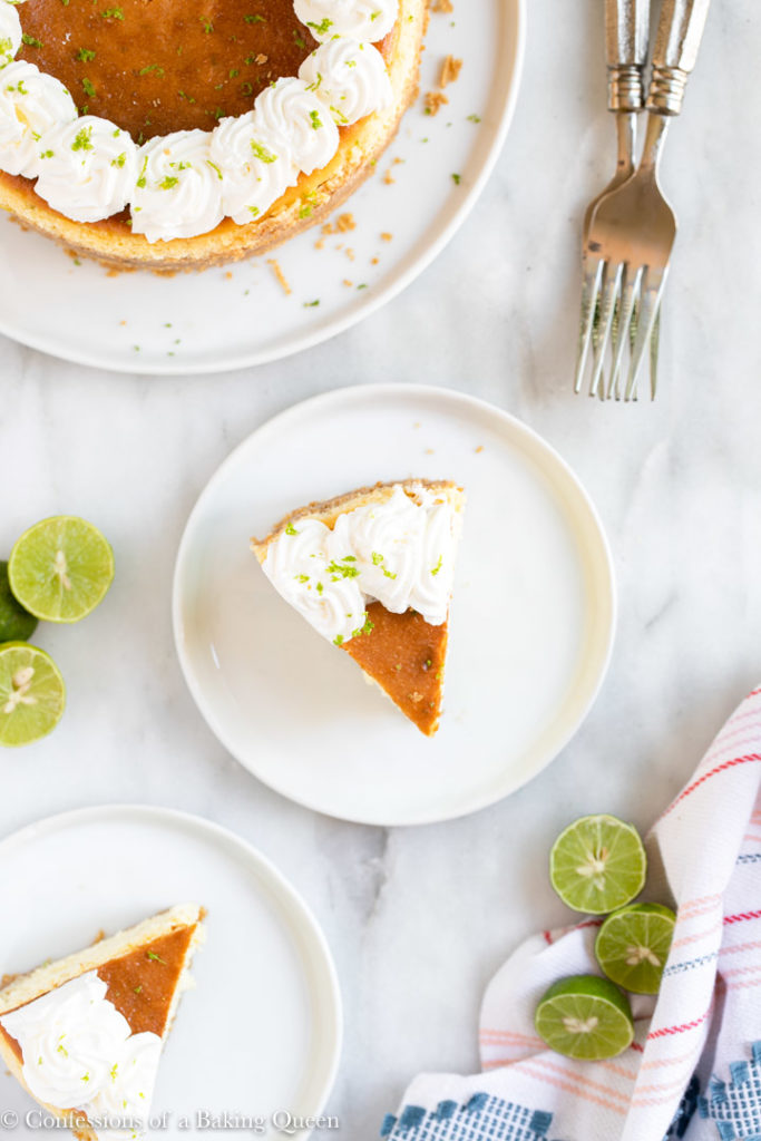 two slices of key lime cheesecake next to the full cake