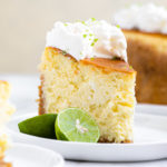 slice of key lime cheesecake with a key lime next to it on a small plate