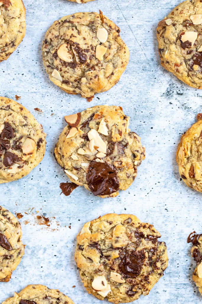 overhead view of almond chocolate chip cookies on a grey surface