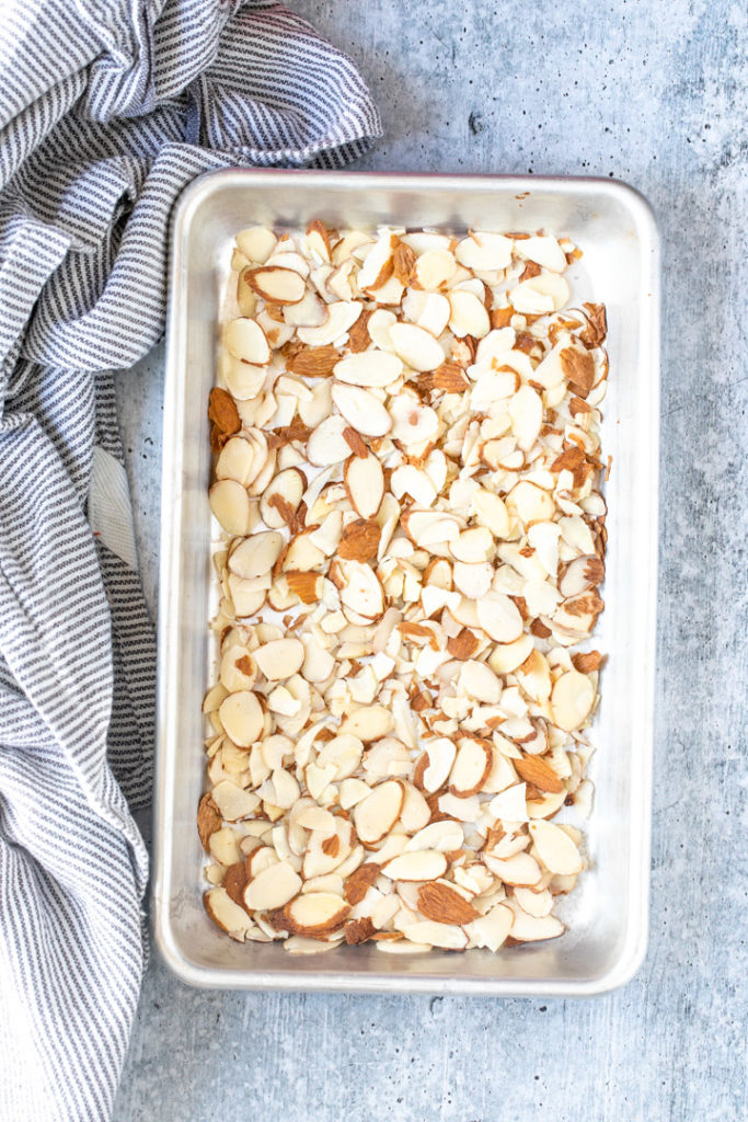 raw almond slices on a small baking sheet