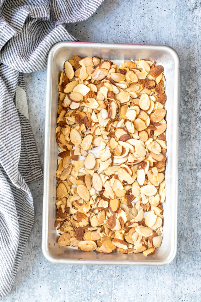 roasted almond pieces on a small baking sheet