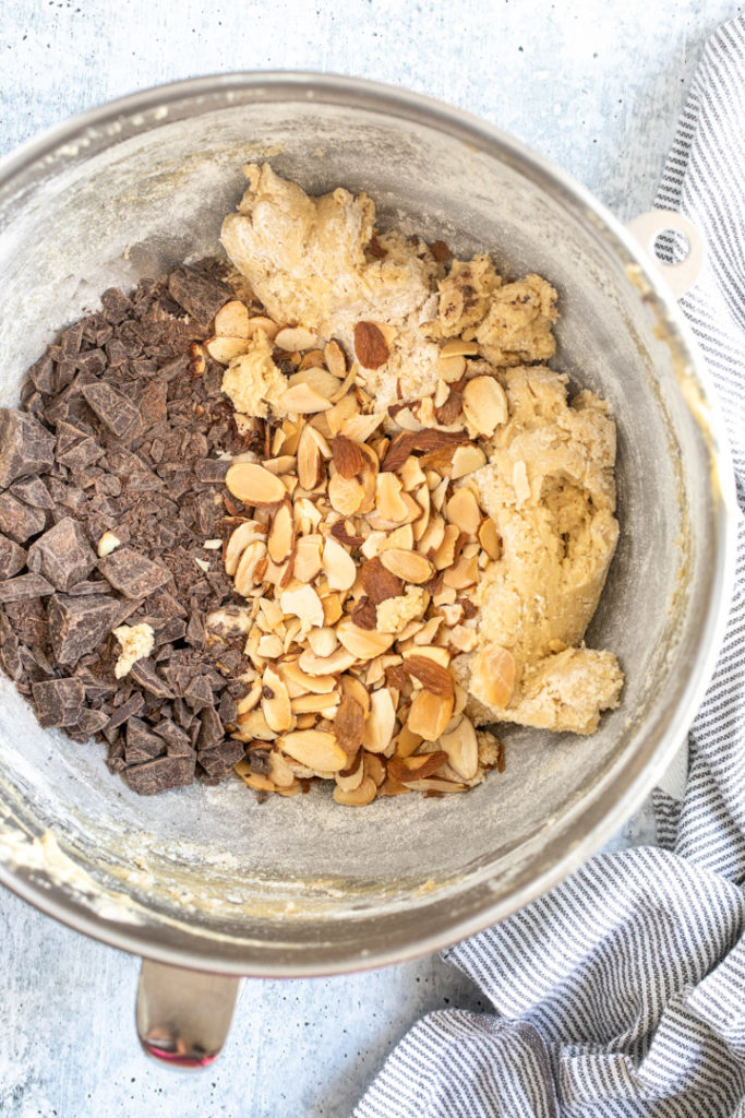 cookie dough with toasted almonds and chocolate chunks in a metal mixing bowl