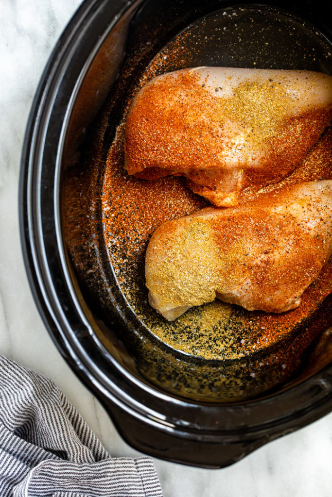 two chicken breasts with spices on in a crockpot