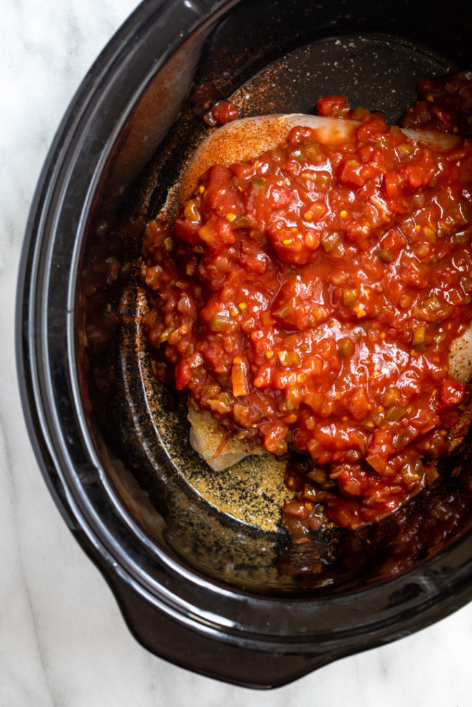 salsa on top of chicken breasts in a black crockpot