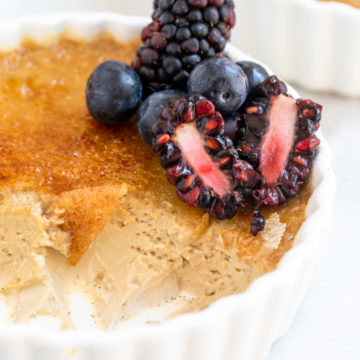 close up of half eaten coffee creme brulee with fresh berries