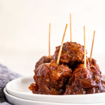 crockpot bbq meatballs with toothpicks sticking out on a white plate on a white plate with a blue linen